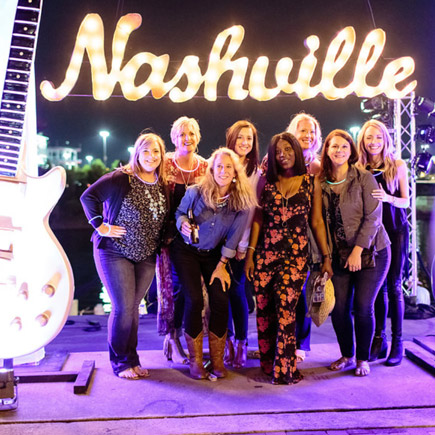 A group of diverse ladies at an incentive program posing for a group picture behind a neon sigh that spells out Nashville