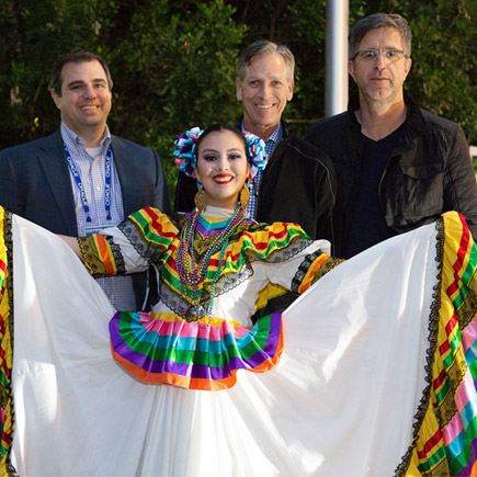 Three businessmen posing for a picture behind a female traditional Mexican dancer
