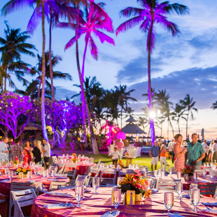 A final night dinner set up along the coast featuring pruple lighting, colorful table set ups and palm trees