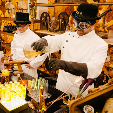 Two males dressed in mad scientist costumes mixing cocktails at a corporate event